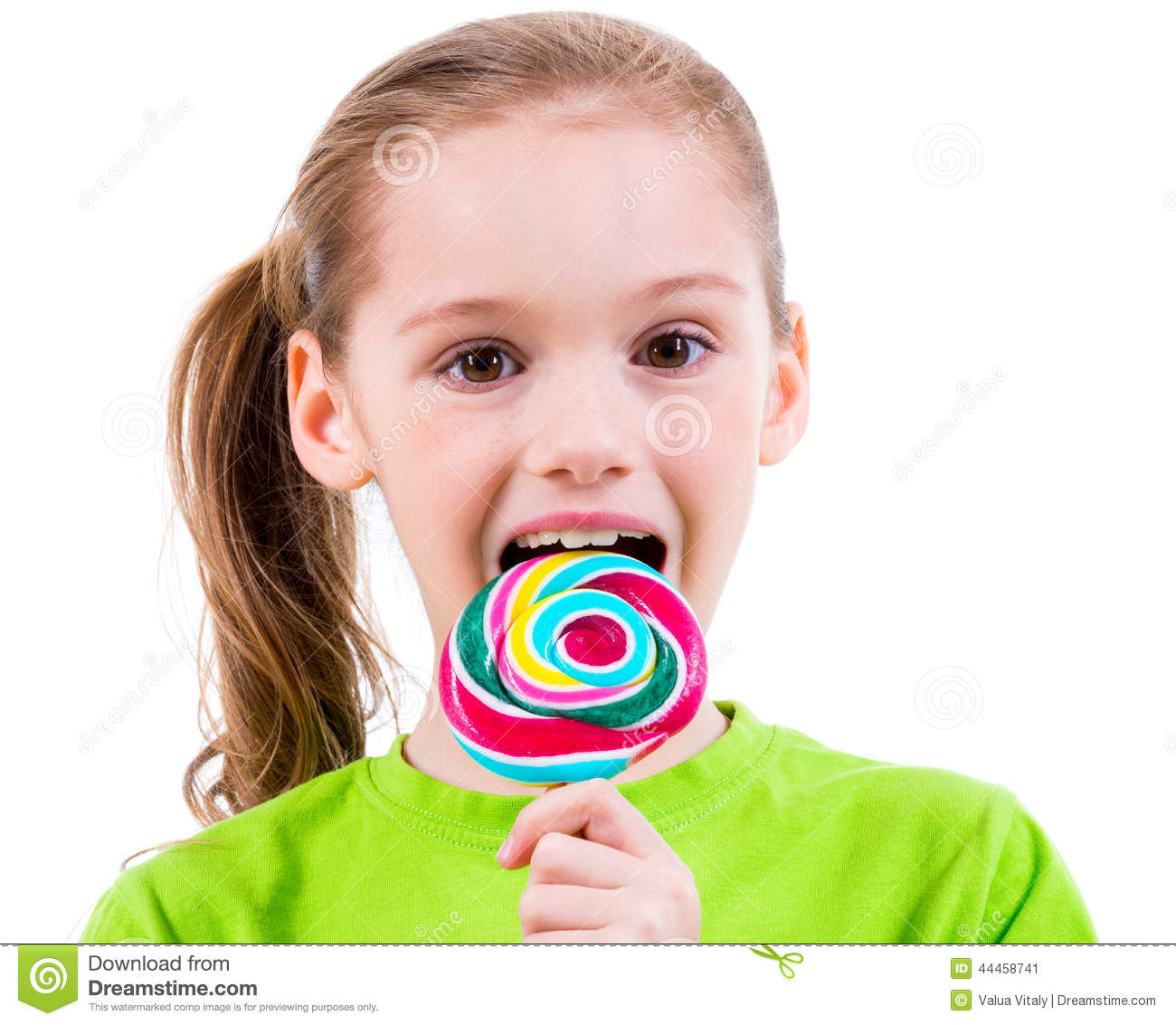 0c1b310f04 Smiling Little Girl In Green T-shirt Eating Colored Candy. Stock ...