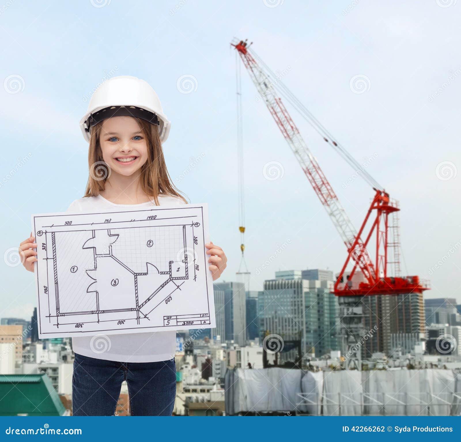 Smiling little girl in helmet showing blueprint