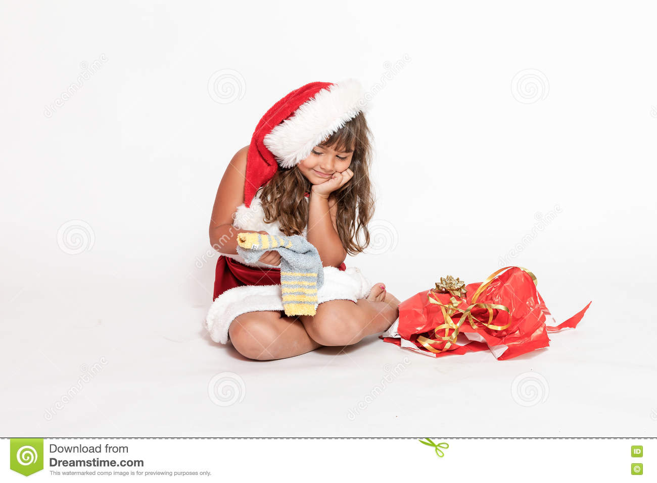 Smiling little girl is looking at an inappropriate gift