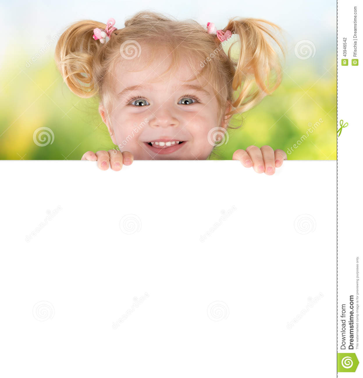Smiling little girl peeking behind a board