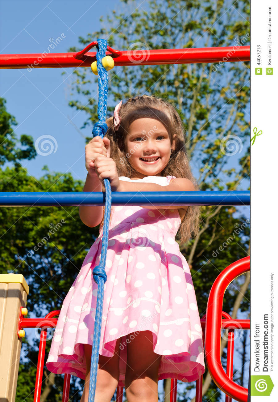 smiling little girl playing on playground equipment stock