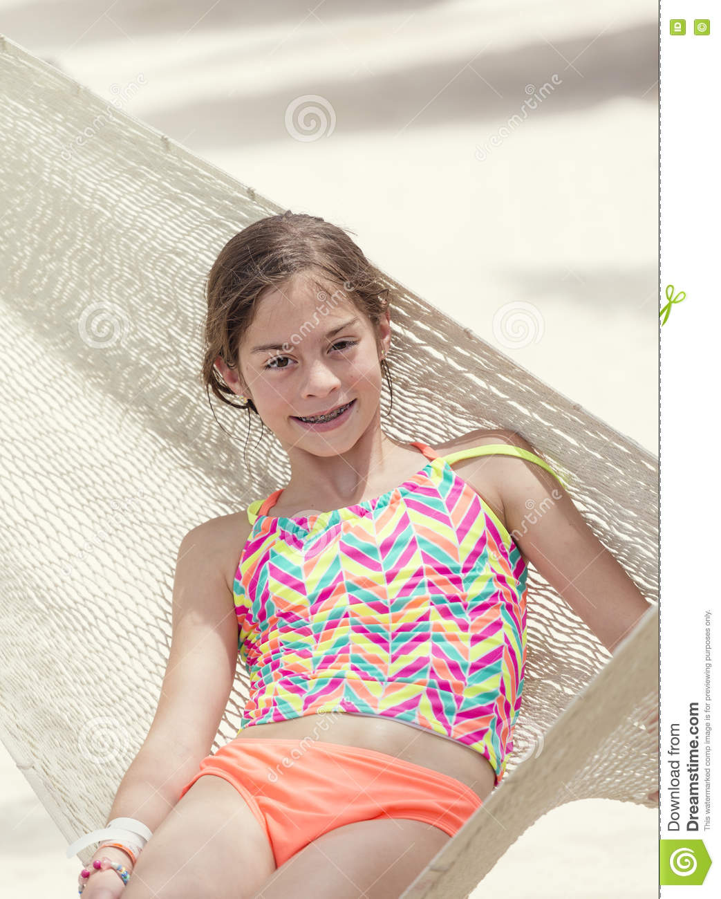 Smiling Little Girl Relaxing In A Hammock On Vacation