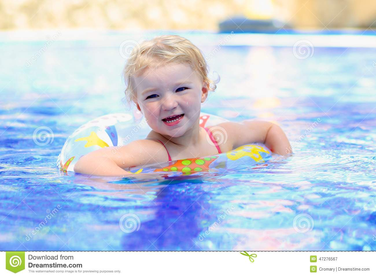 Adorable happy little child, curly toddler girl in swimming suit ...