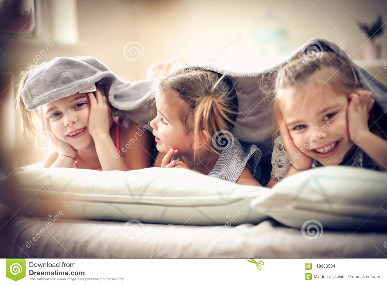 Smiling little girls in bed.