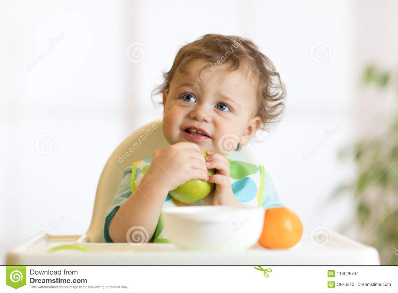 Smiling little kid child baby boy sitting in highchair and eating big green apple fruit portrait indoors