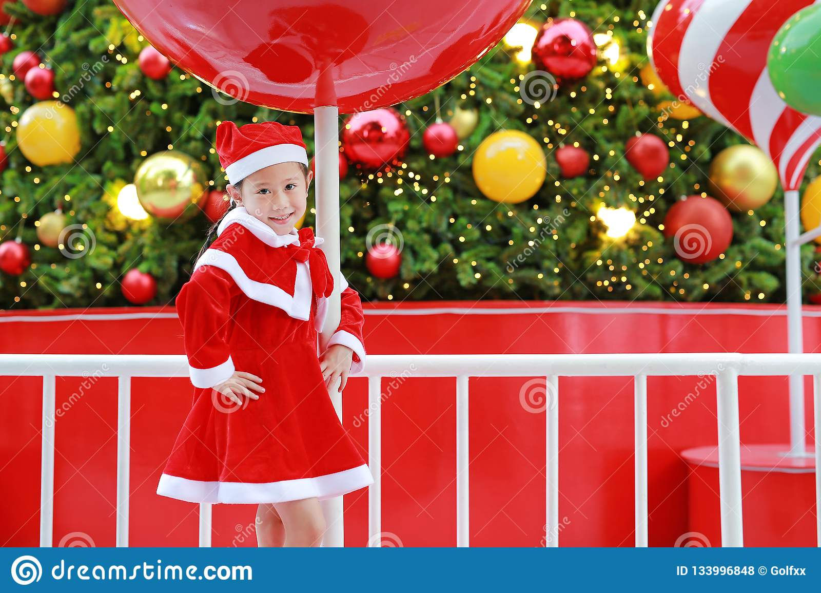 Smiling little kid girl in Santa costume with Christmas background. Merry Christmas and happy holidays