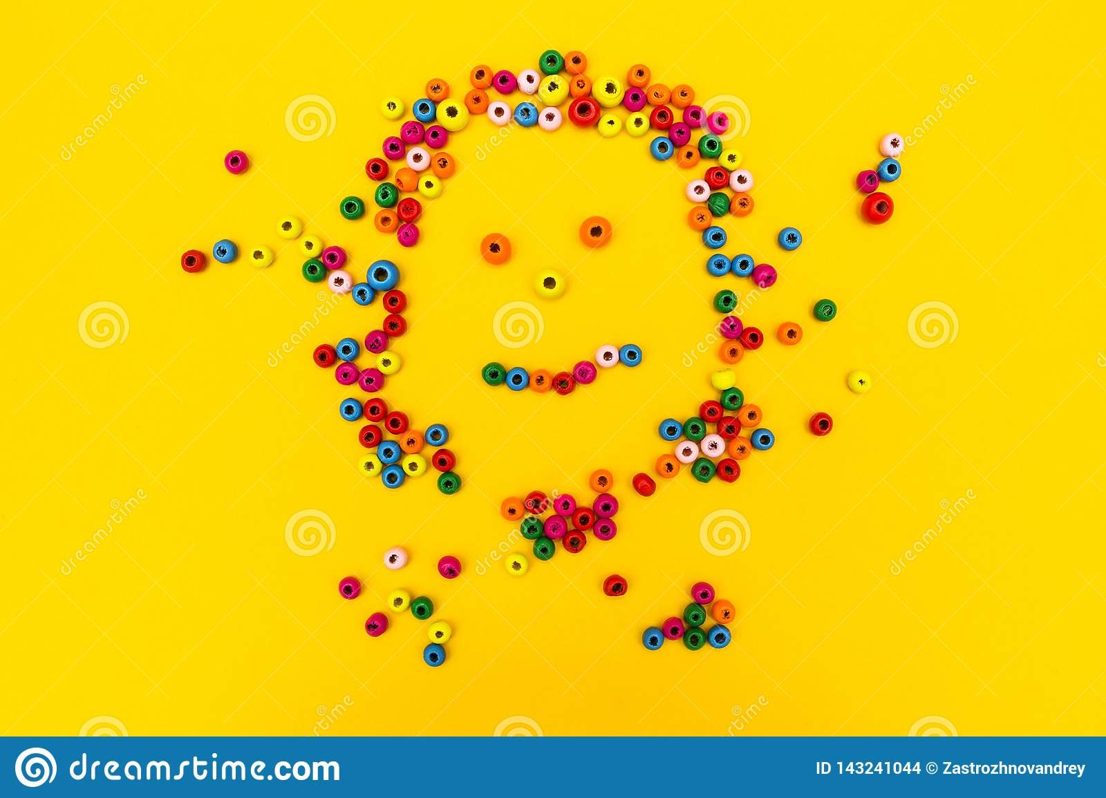 Smiling little man smiley from multi-colored round toys on a yellow background