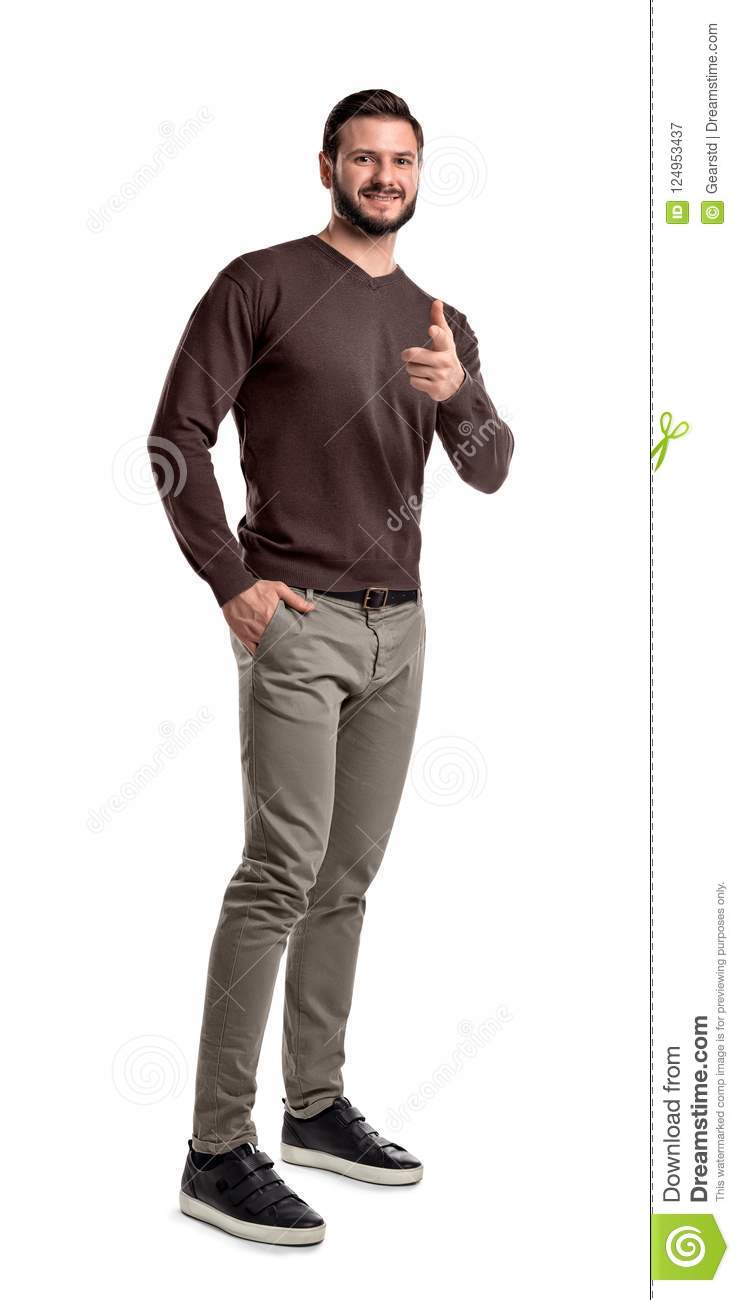 1114a212d2e6 A smiling man in casual wear looks on a white background and points with  his index finger at camera.