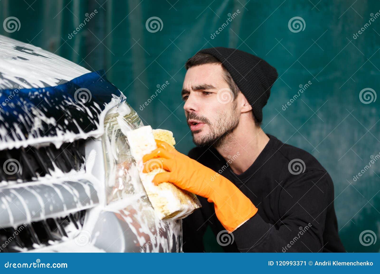 A smiling man washes a grey car