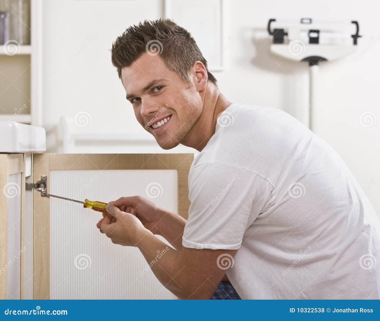 Amazing Smiling Man Fixing Cabinet Door
