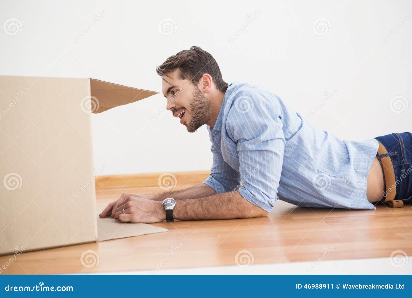 smiling man looking inside cardboard box stock photo image 46988911. Black Bedroom Furniture Sets. Home Design Ideas