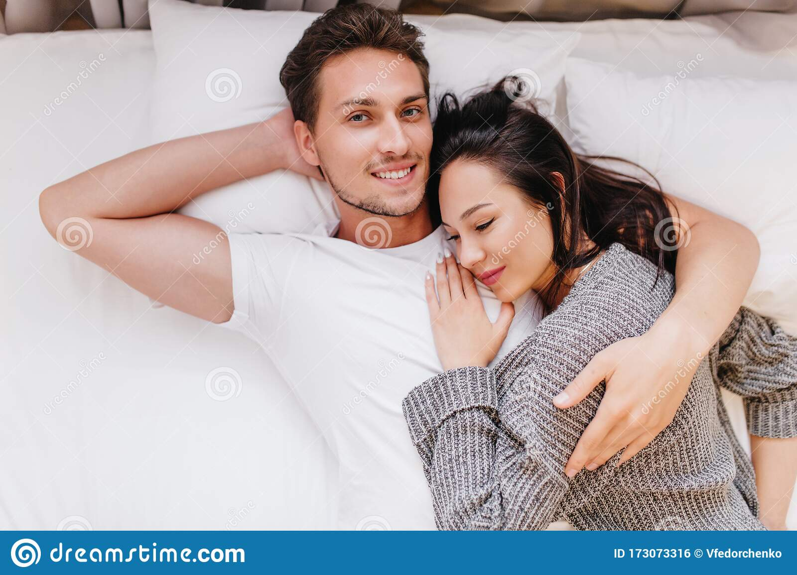 Smiling Man Posing In Bed With Wife Sleeping On His Chest Indoor Overhead Photo Of Chilling Couple Spending Weekend Stock Photo Image Of Joyful Boyfriend 173073316
