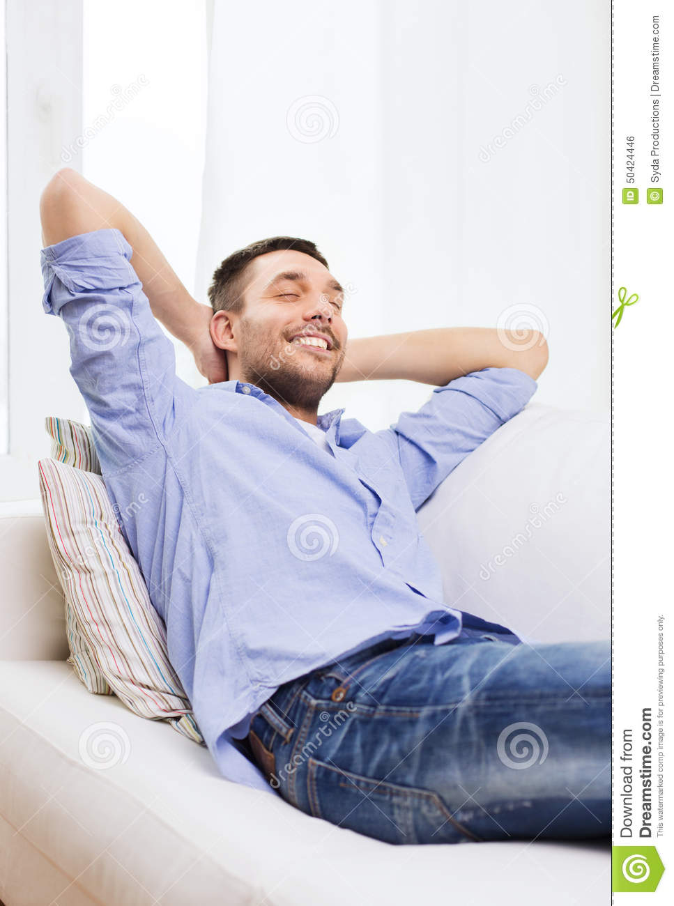 Smiling Man Relaxing On Couch At Home Stock Photo - Image ...