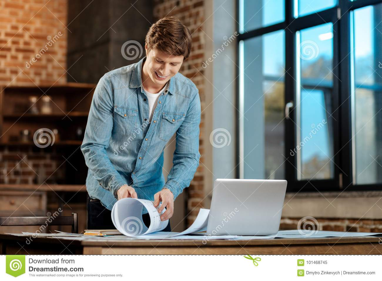 Smiling Man Rolling A Blueprint In The Study Stock Image