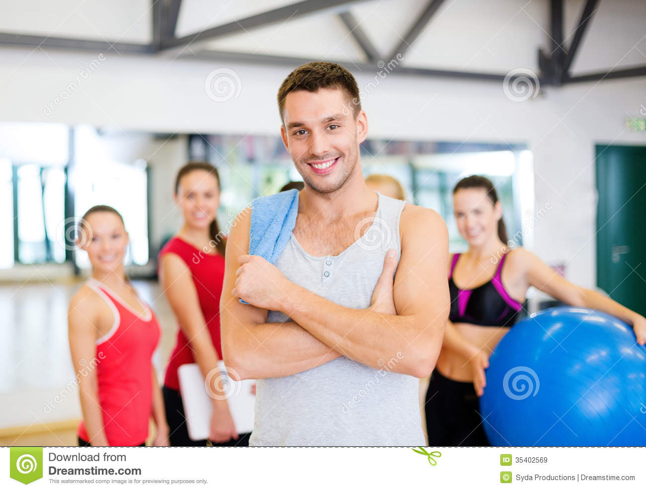 Smiling man standing in front of the group in gym stock for Gym life fitness