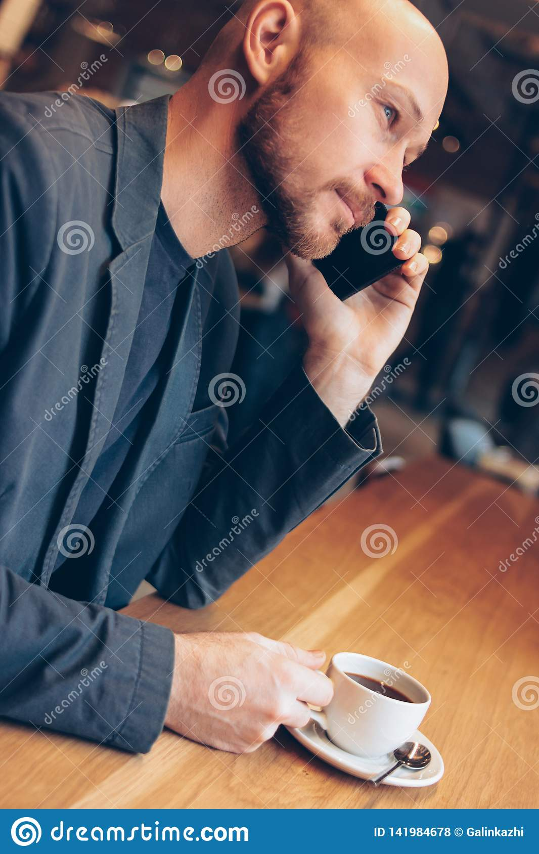 The smiling man in suit speaking on mobile phone, sitting with coffee at cafe