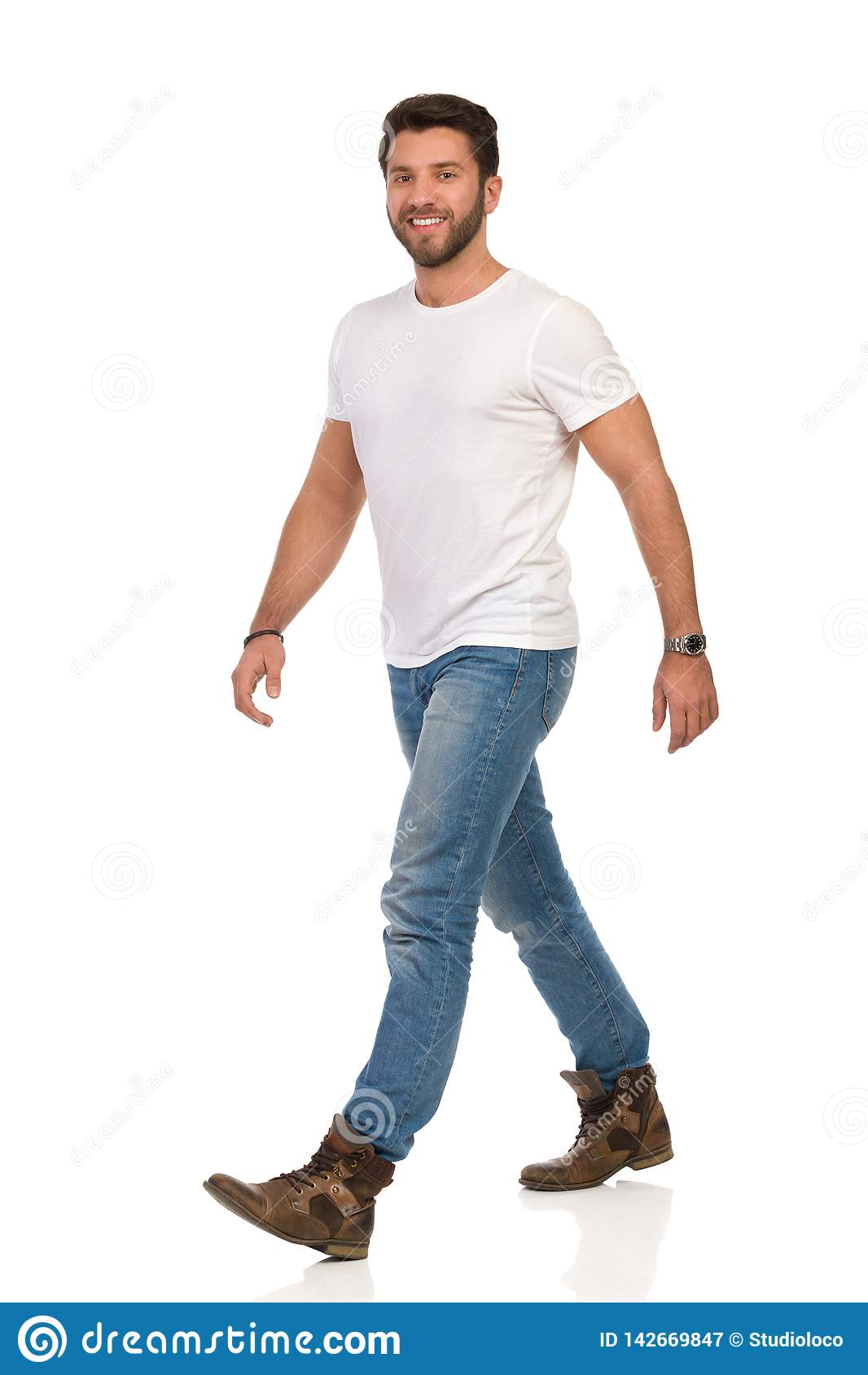 Smiling Man In White T,shirt, Jeans And Boots Is Walking