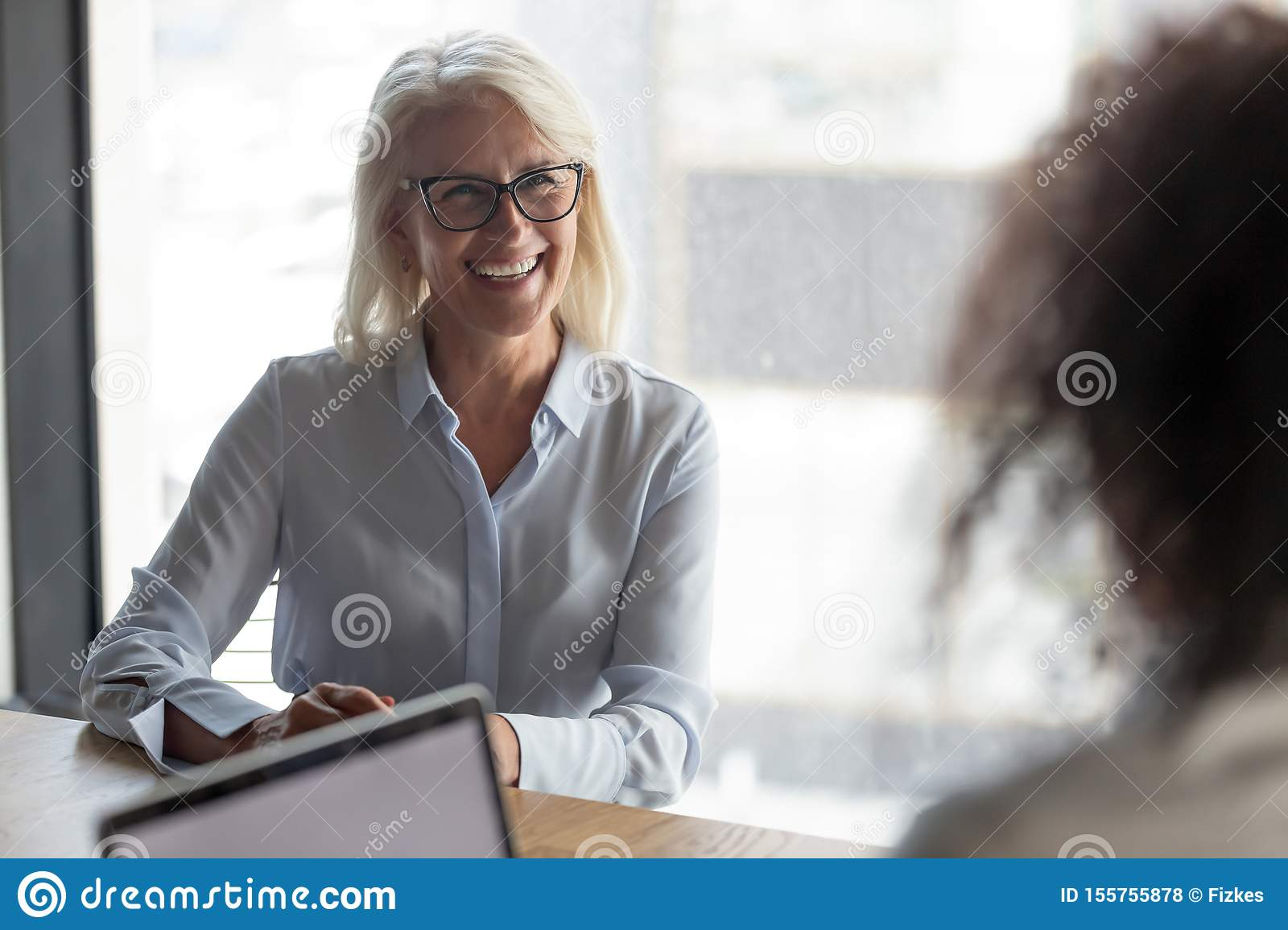 Smiling mature businesswoman candidate answering hr manager questions