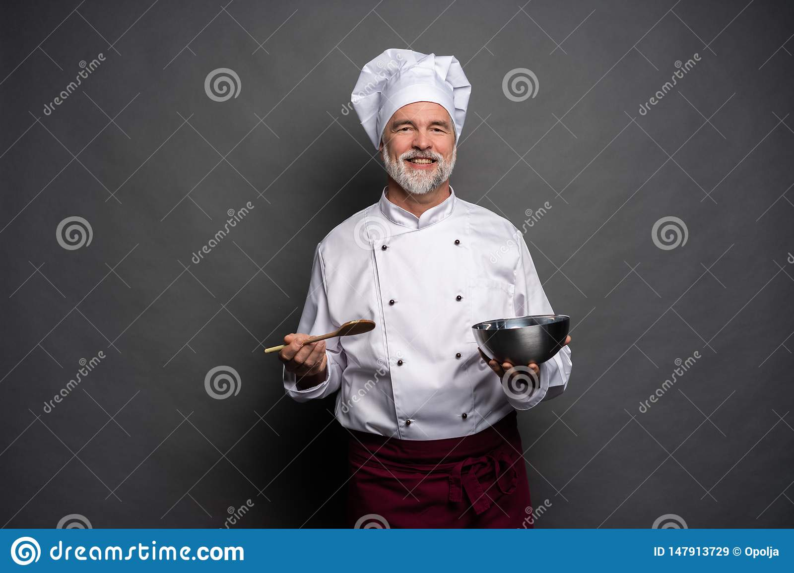 Smiling mature male chef with bowl and cooking vane in hands on black background.
