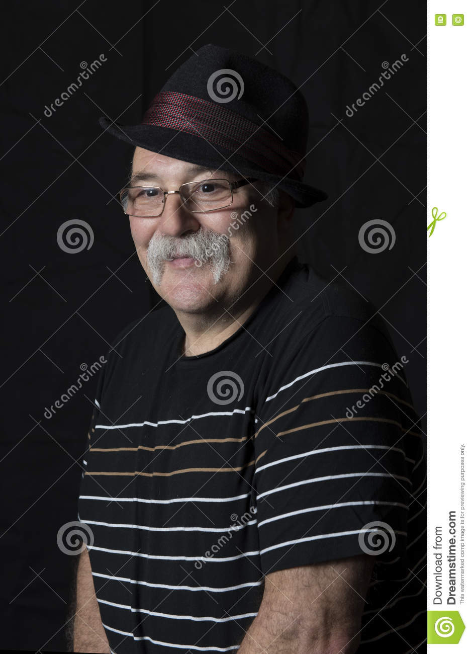 Smiling mature man with a hat and glasses.