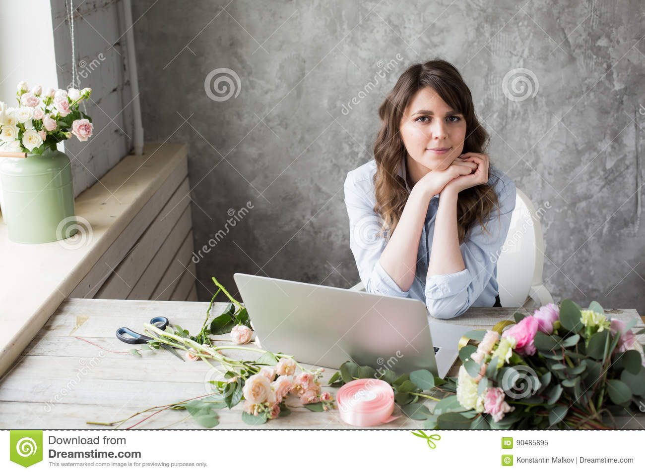 Smiling Mature Woman Florist Small Business Flower Shop Owner. She is using her telephone and laptop to take orders for