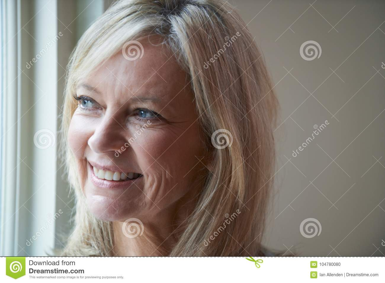 Smiling Mature Woman Standing Next To Window