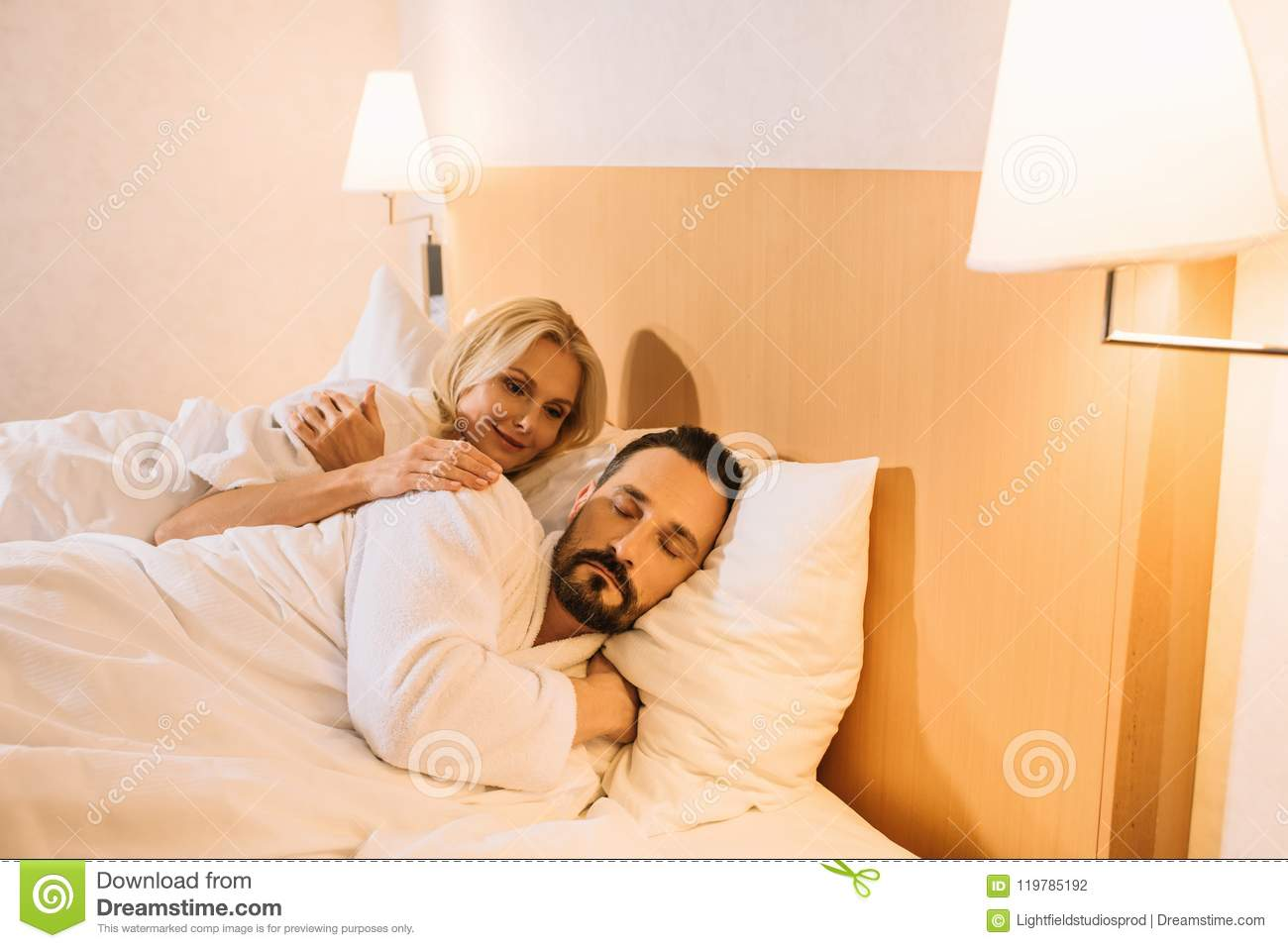 smiling mature woman in bathrobe looking at her husband sleeping