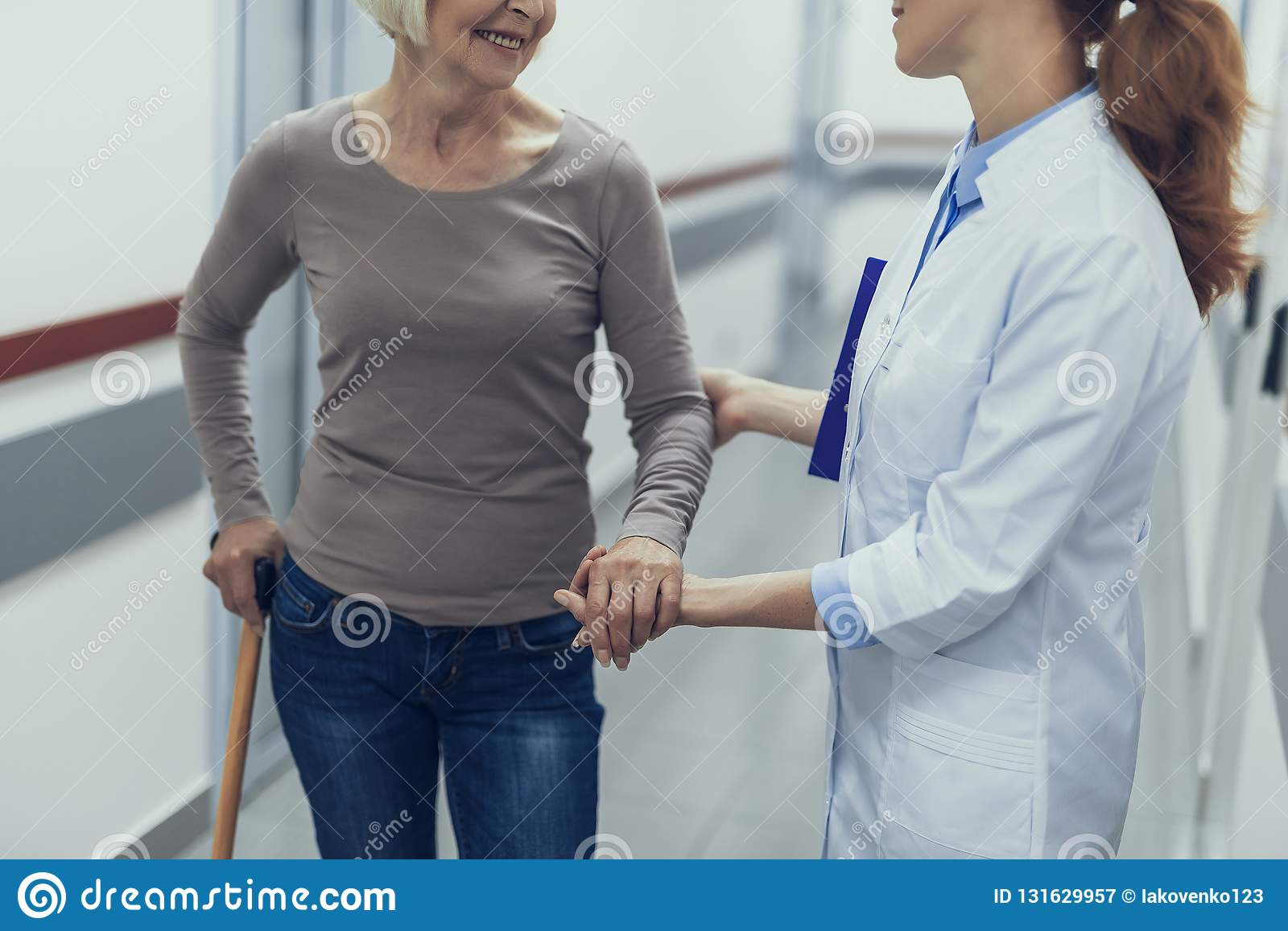 Female doctor is supporting aged lady by hand