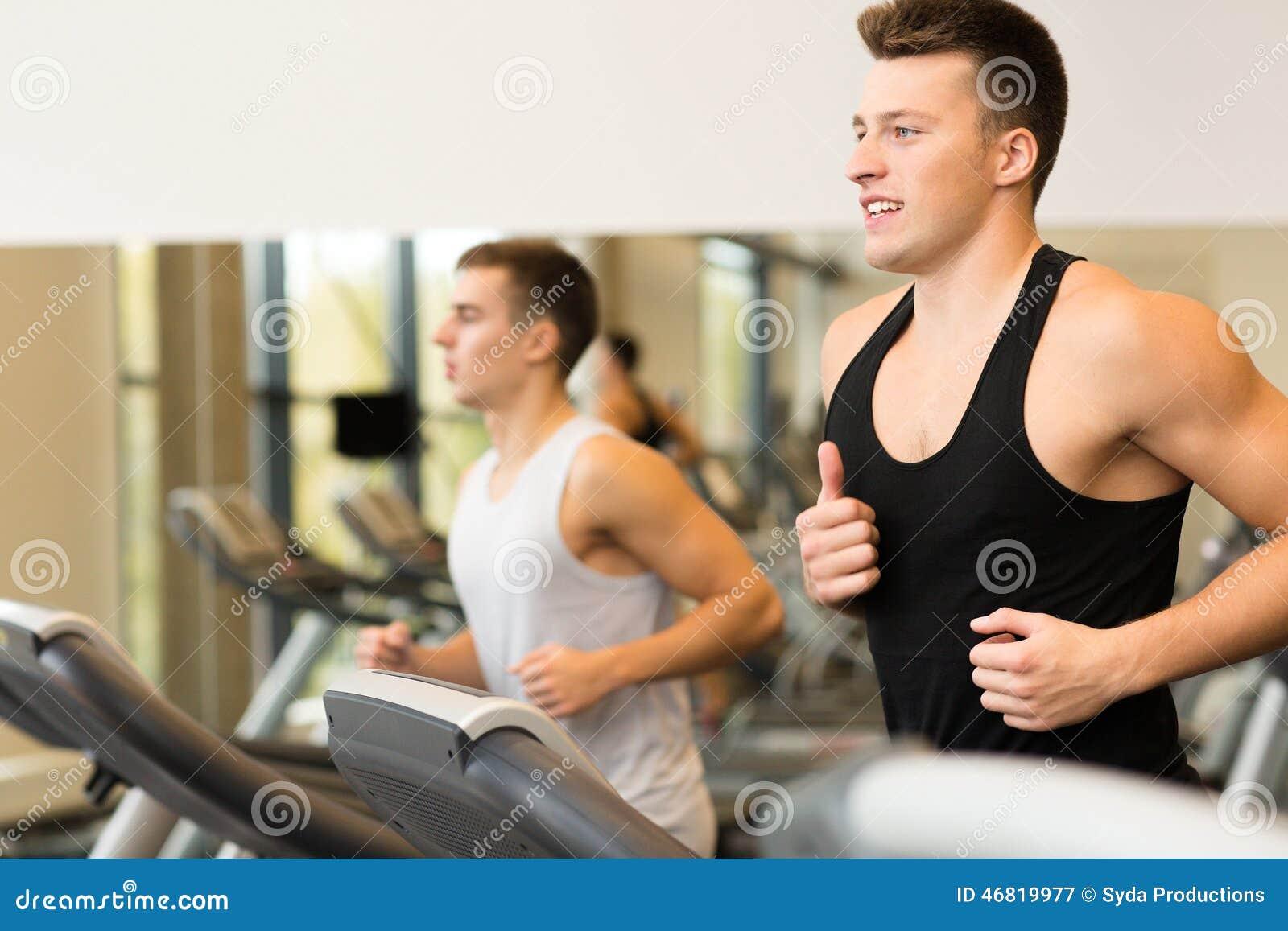 Smiling men exercising on treadmill in gym