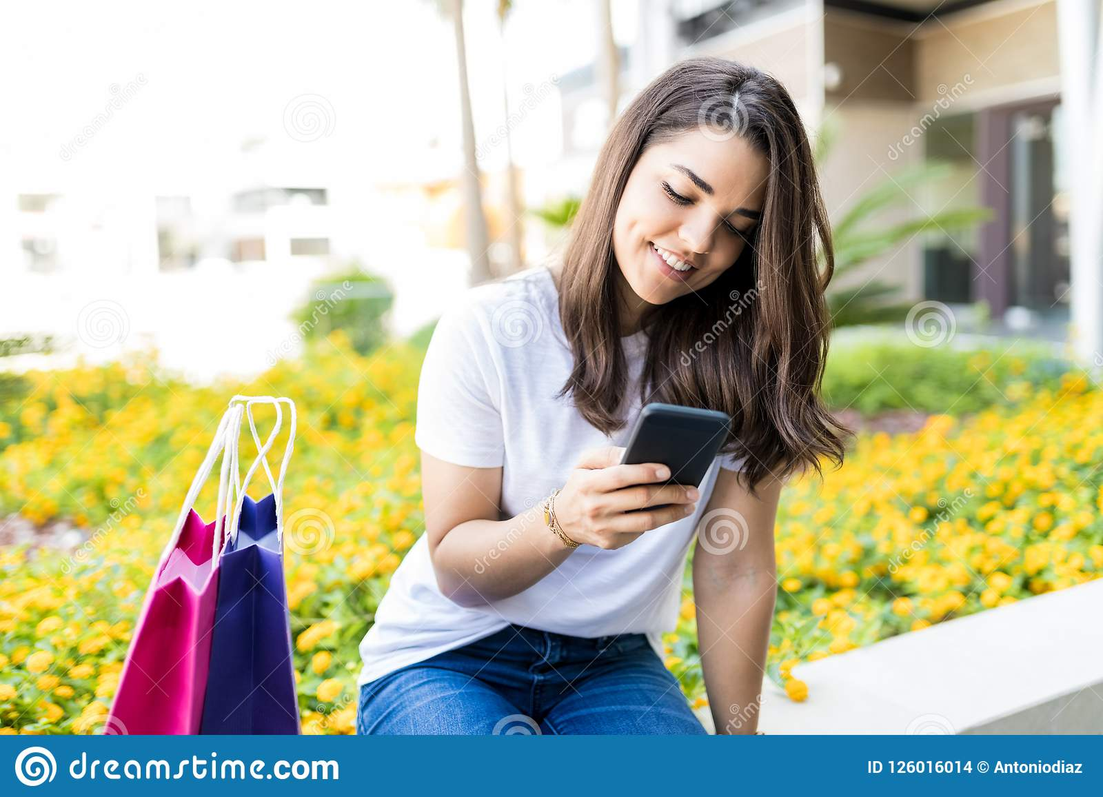 Female Texting On Mobile Phone While Sitting By Shopping Bags