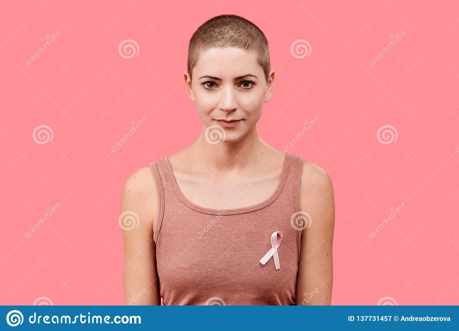 Smiling mid 30s woman, a cancer survivor, wearing pink breast cancer awareness ribbon, isolated over living coral background.