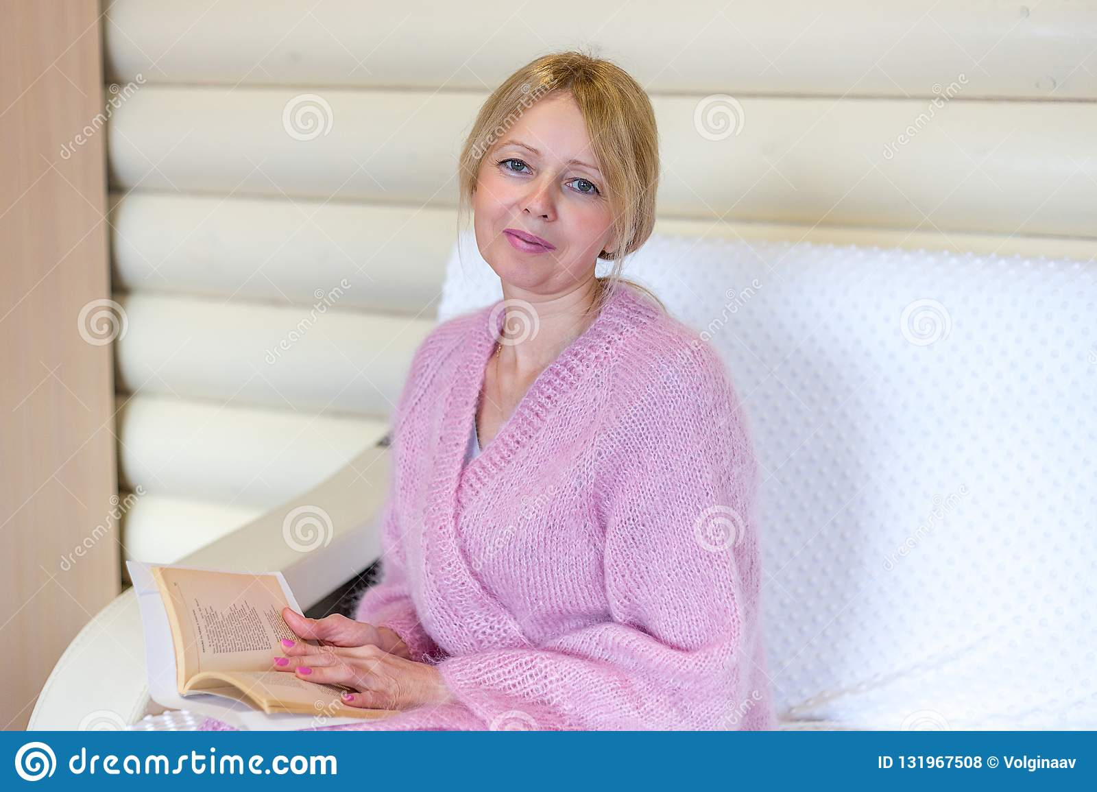 Smiling middle age woman reading a book at home