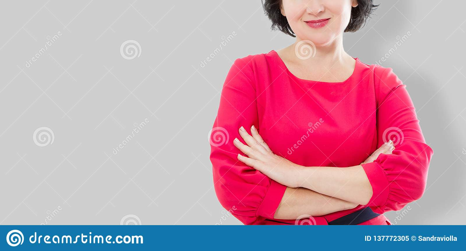 Smiling Middle age woman in red dress and crossed arms isolated on gray background. Make up and beauty concept. Copy space.