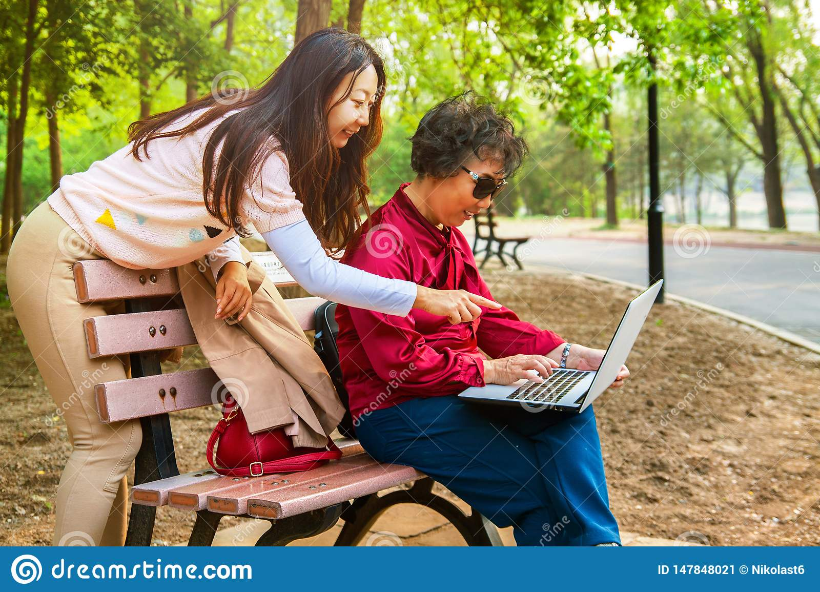 Mother and daughter using a laptop at garden. Daughter teaches an elderly mother to use a computer.
