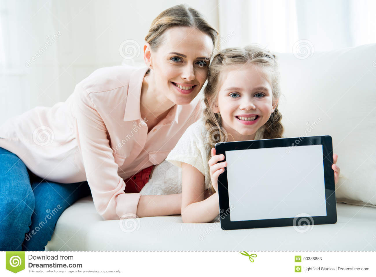 Smiling mother and daughter showing digital tablet