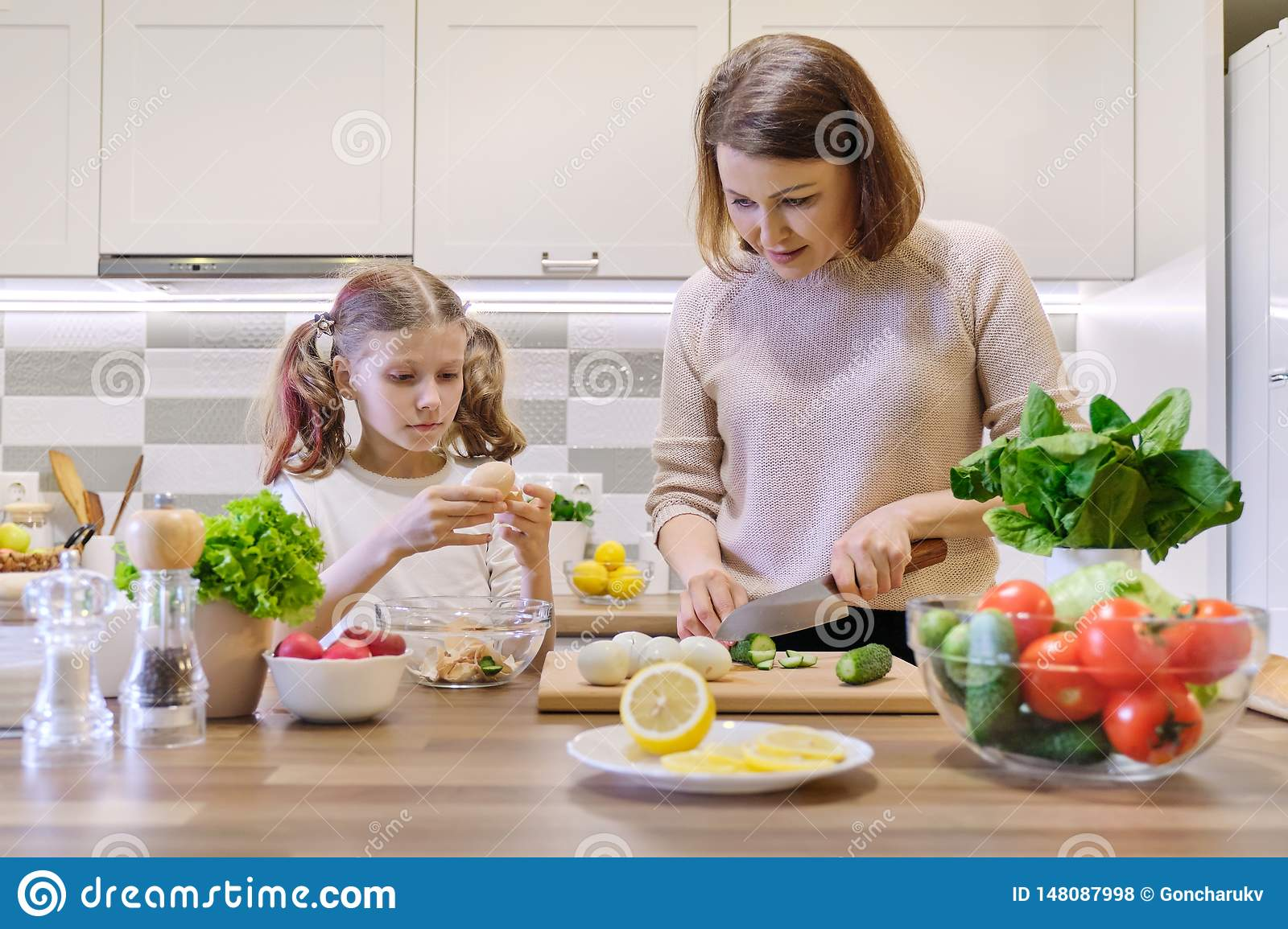 Smiling mother and daughter 8, 9 years old cooking together in kitchen vegetable salad. Healthy home food, communication parent