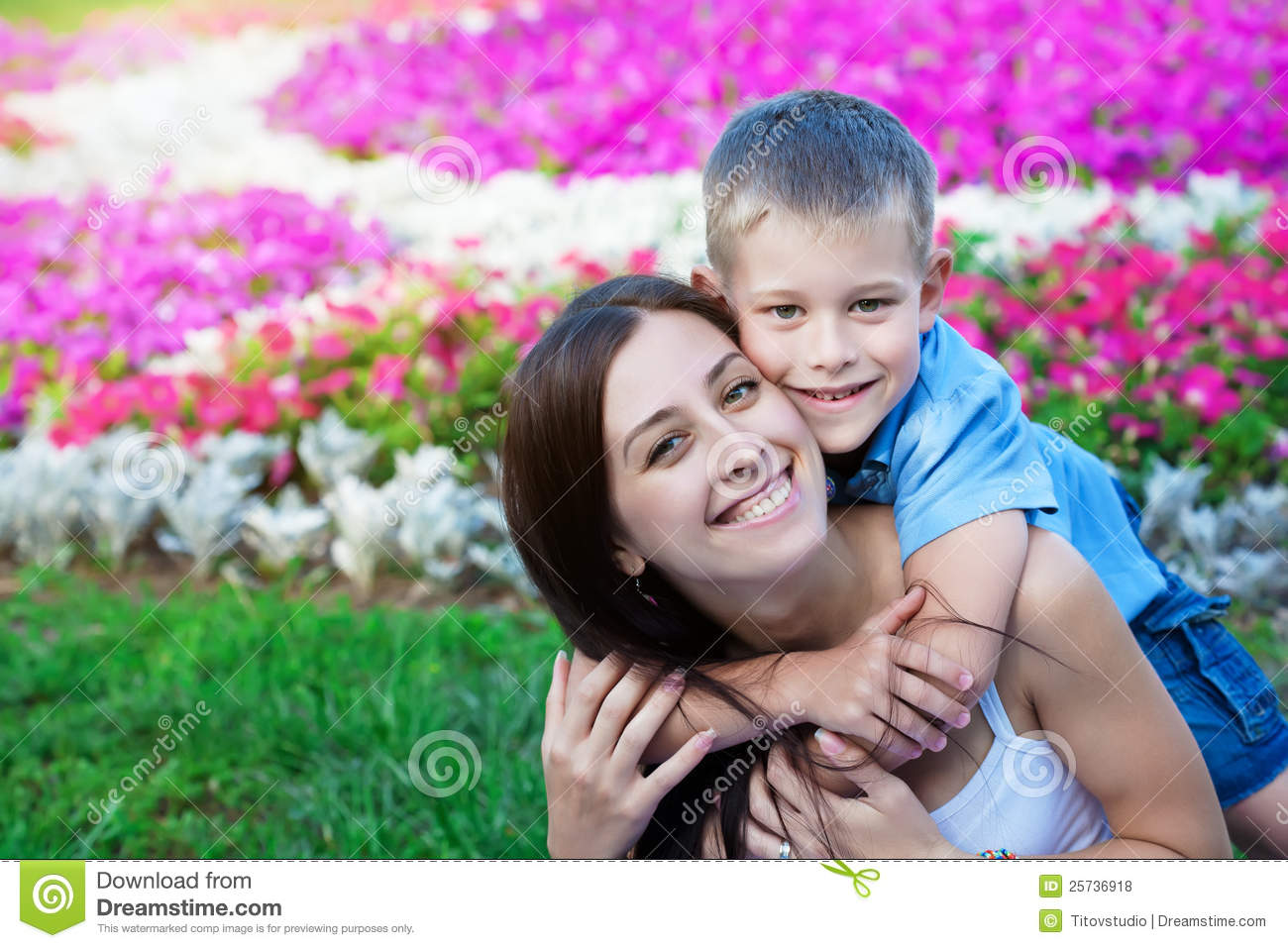 Smiling Mother and son siting on grass