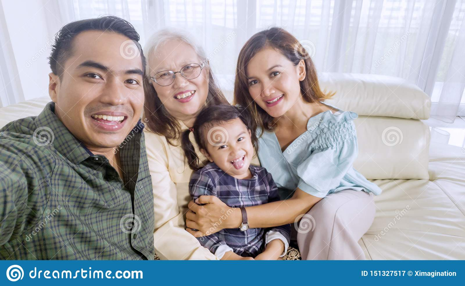 Smiling family takes a group picture at home