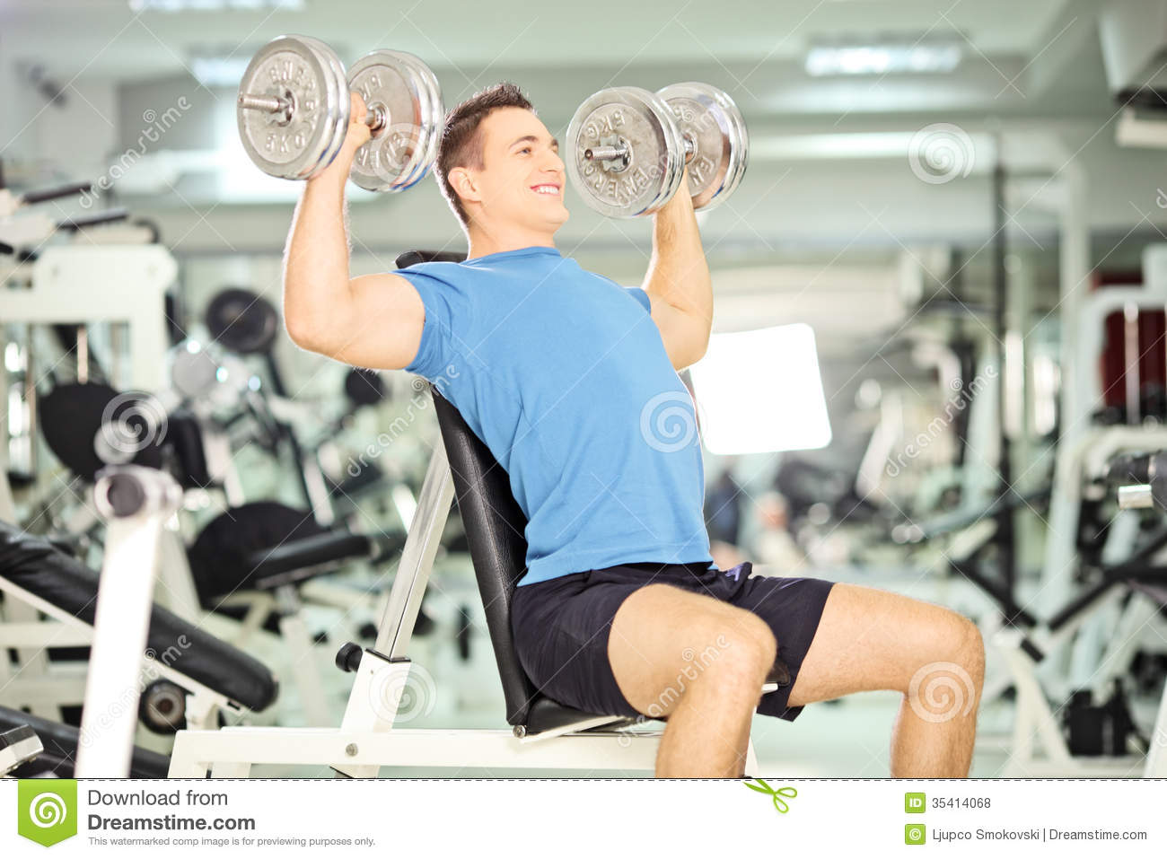 Smiling muscular guy lifting weights in gym club stock for Club gimnasio