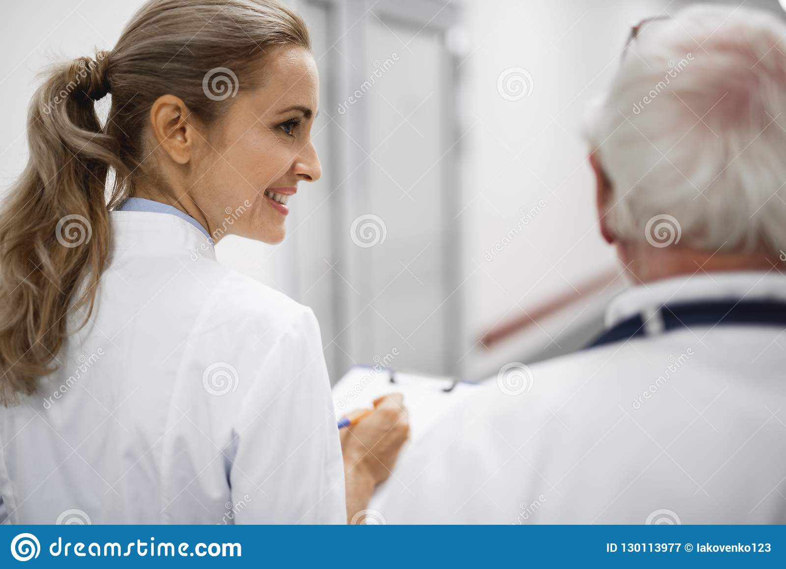 Smiling nurse looking at doctor while they walking in hospital hallway
