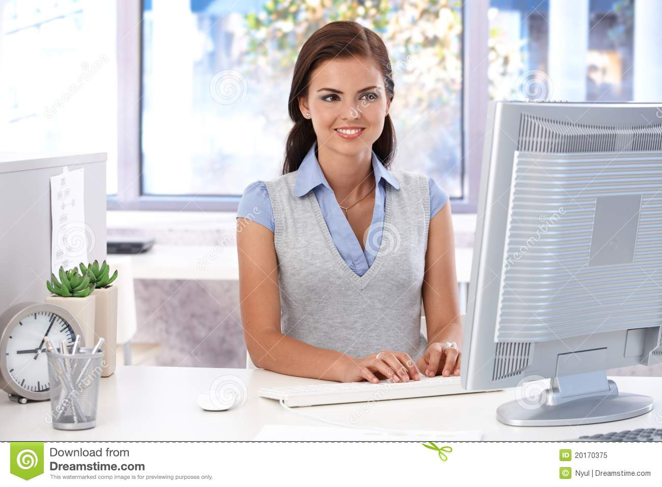 Female Office Worker Using Computer And Telephone At Desk Stock ...