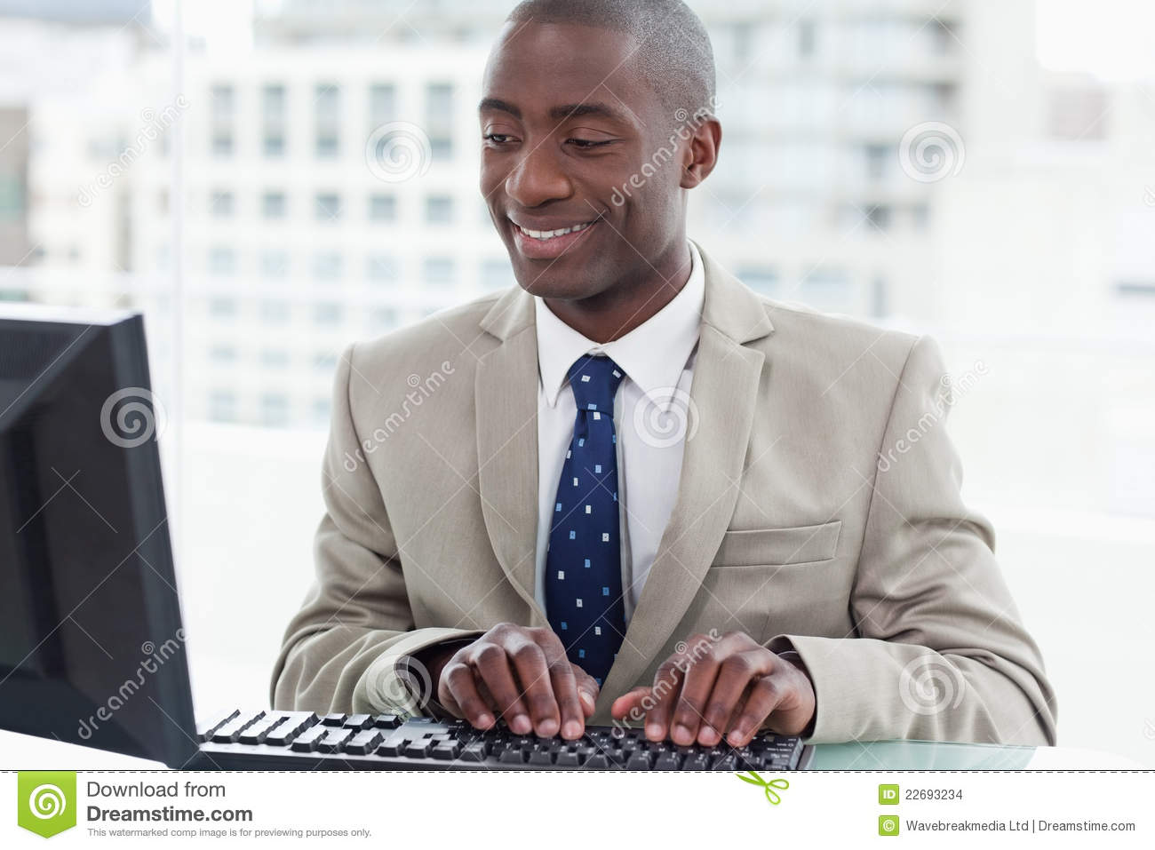 Smiling office worker using a computer in his office. mr: yes; pr: no