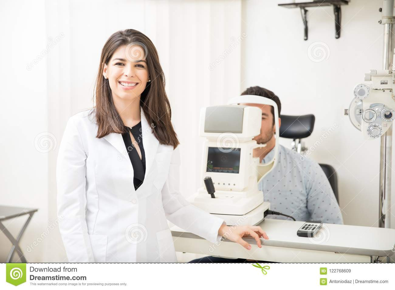 9c52fbe071a Portrait of beautiful smiling women wearing labcoat standing in  ophthalmology clinic with men patient sitting for eye test in background