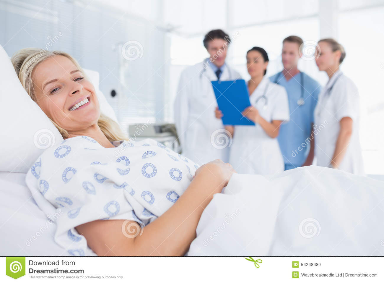 smiling patient looking at camera with doctors behind