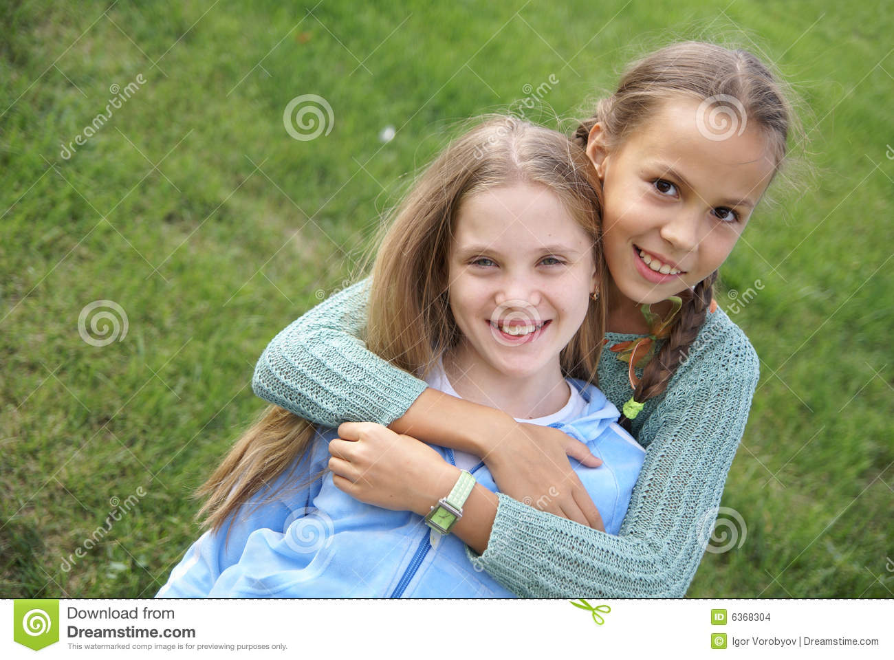 Smiling preteen girls outdoors on green grass background.