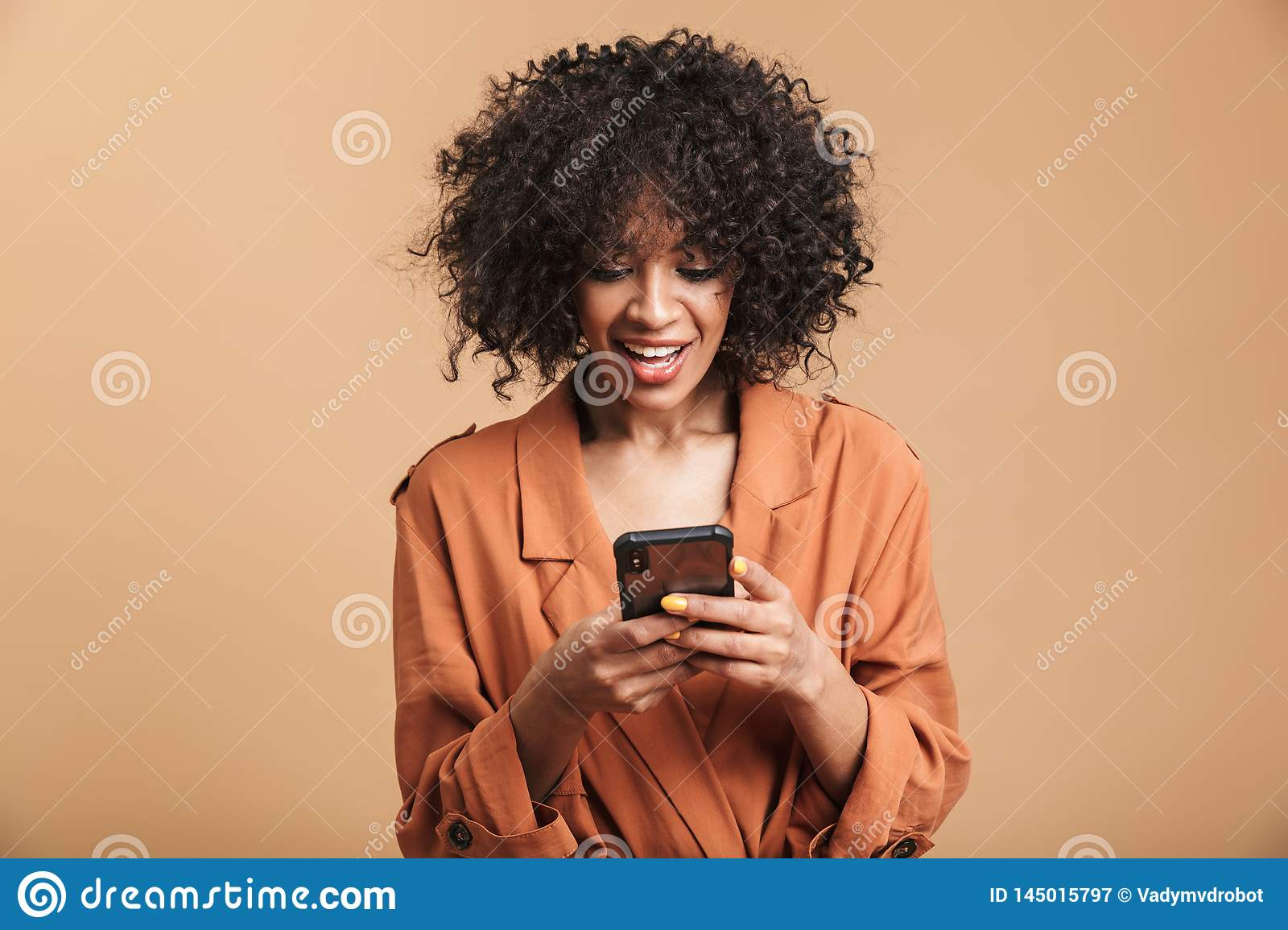 Smiling pretty african woman writing message on smartphone