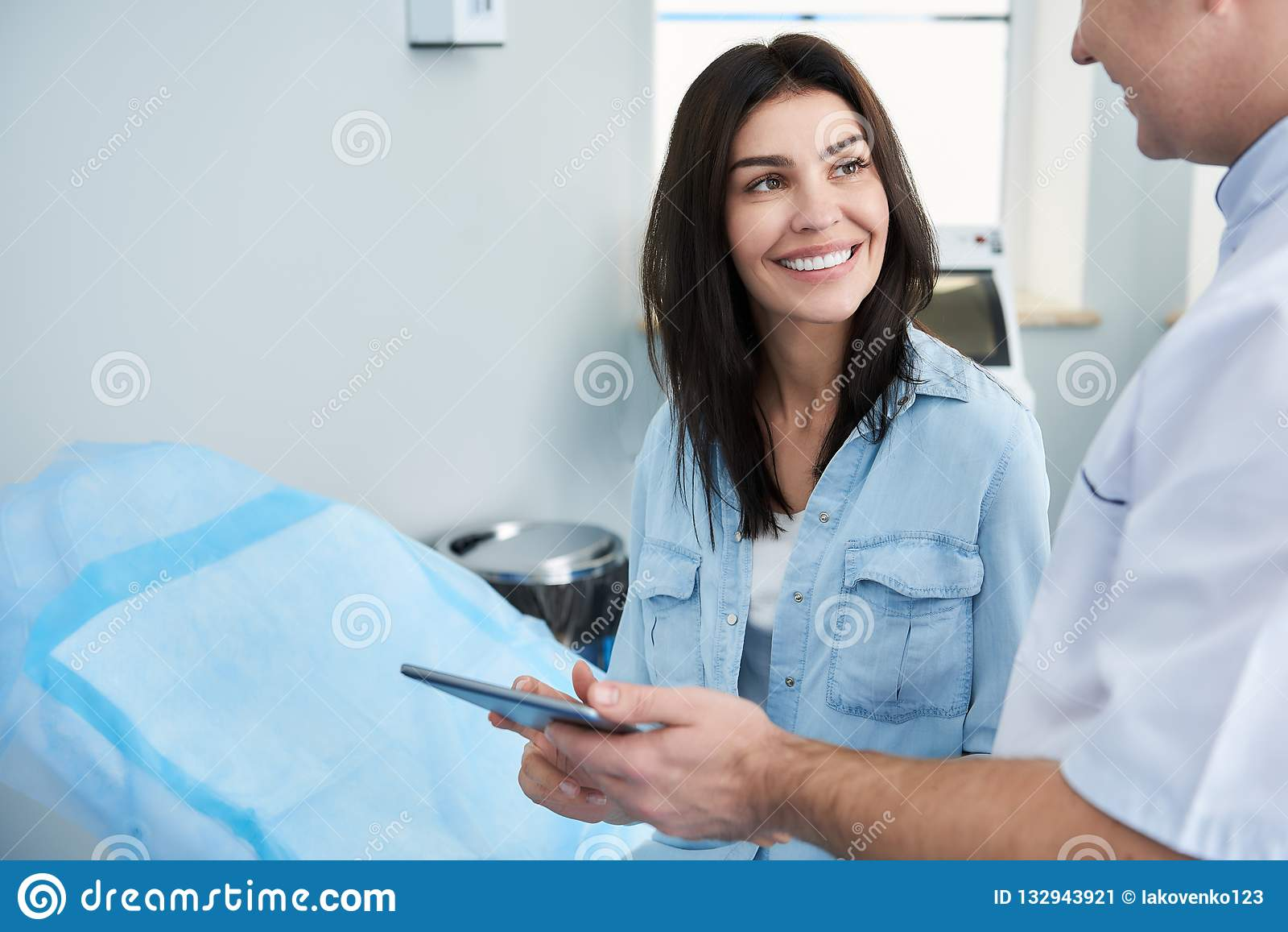 Smiling pretty woman is talking with surgeon