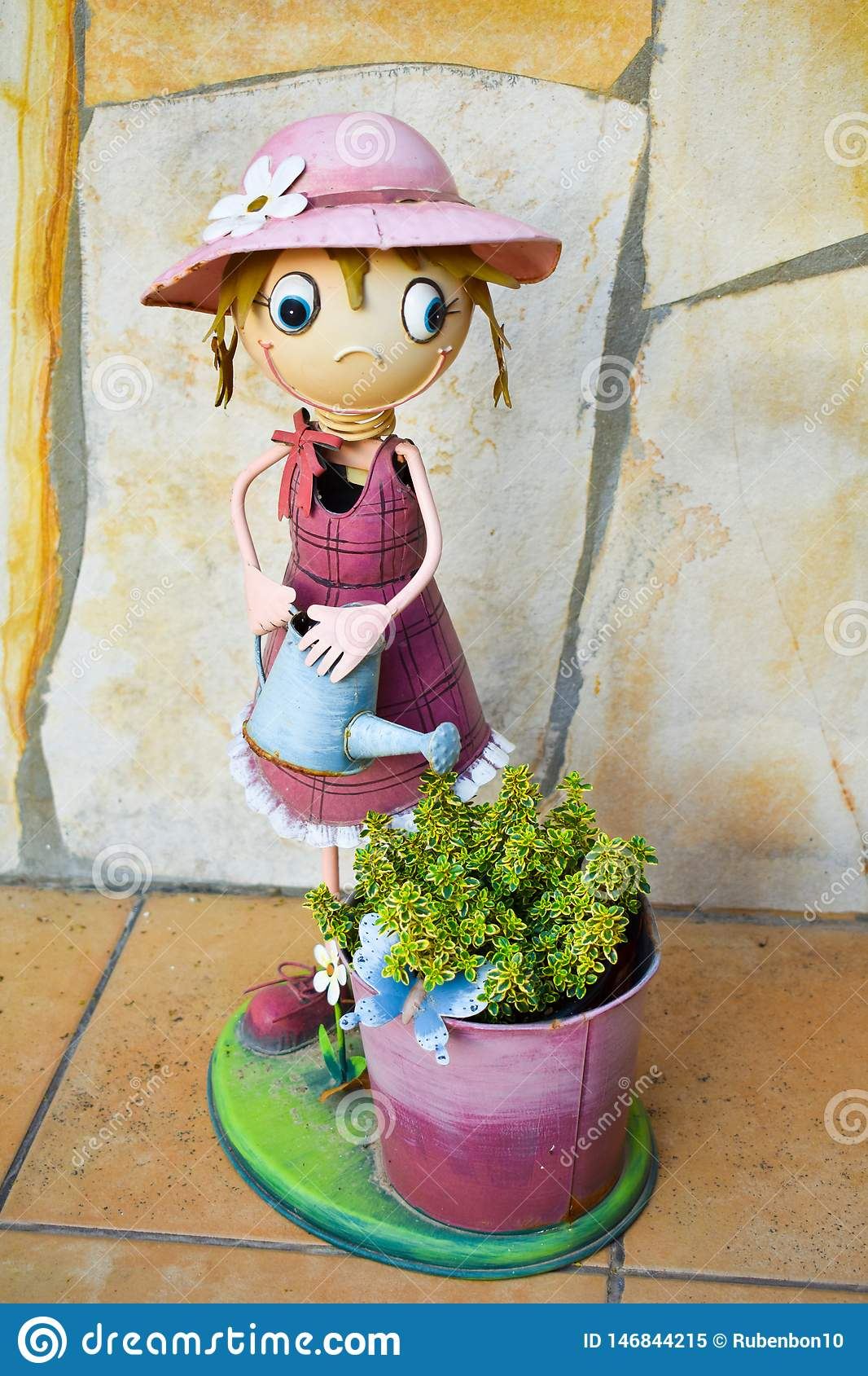 Smiling puppet made in colorful steel that shows a happy cross-eyed girl watering can a bucket with a green plant on a yellow