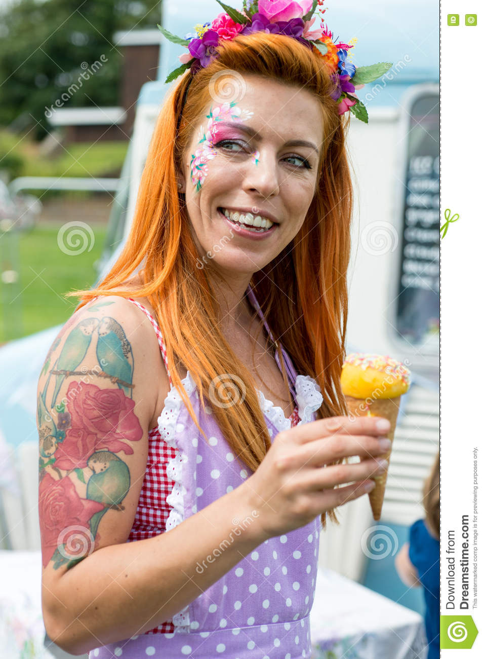 Smiling red haired lady wearing vintage dress holding ice cream