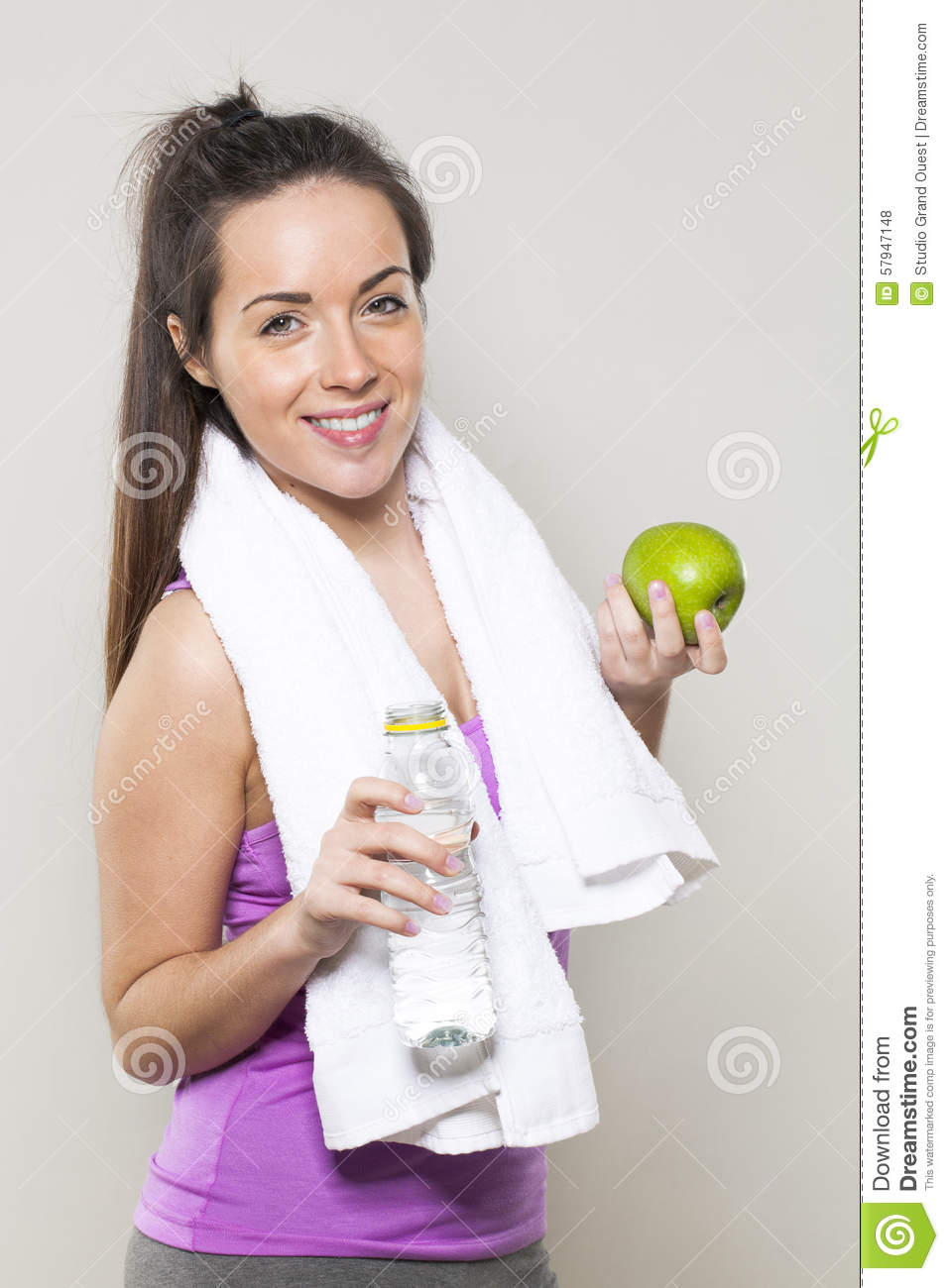 Smiling 20s athletic girl with symbols of health and nutrition for sporty lifestyle in hands